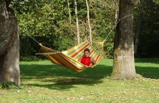 Hangmat tussen twee bomen in de tuin is genieten van natuurgeluiden